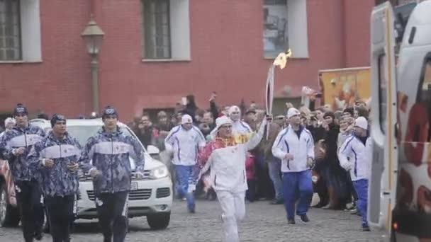 SAINT PETERSBURG, RUSSIA - OCTOBER 27, 2013: Relay race Olympic flame in Saint Petersburg in October. Running torchbearer wave hand to people