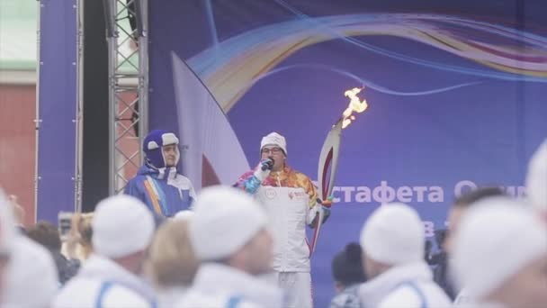 SAINT PETERSBURG, RUSSIA - OCTOBER 27, 2013: Relay race Olympic flame in Saint Petersburg in October. Torchbearer with flame speak on stage