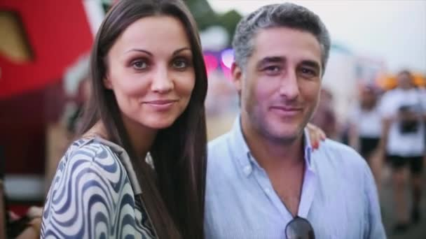 Young attractive woman and aged man smiling in camera. Dating couple. Summer evening. Portrait