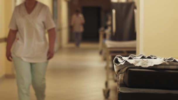 Pohled na chodbu v porodnici. Zdravotní sestry a lékaři v lékařských uniformě. Porodnici