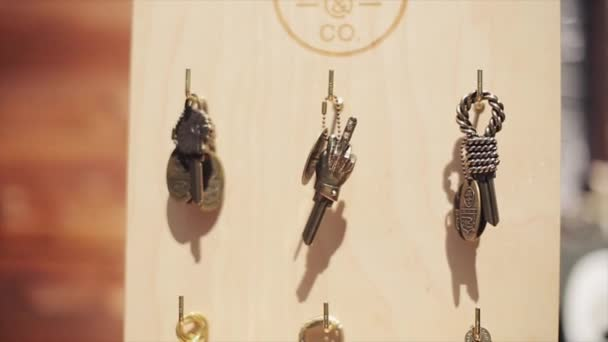 MOSCOW, RUSSIA - JULY 27, 2015: View of iron little trinket different figures hang at wooden board. Middle finger, lion head. Sunny