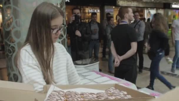 Saint Petersburg, Oroszország - 2016. június 4.: Lány és az ember tegye színes fánk asztalra bevásárlóközpontban. Tisztességes. Az emberek