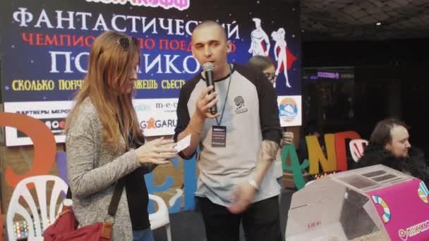 Saint Petersburg, Oroszország - 2016. június 4.: Férfi mikrofon ad lány szelvény lottó mezőből. Bevásárló központ. Az emberek