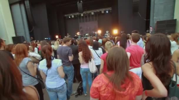MOSCOW, RUSSIA - AUGUST 23, 2011: Back side of people at summer live concert. Music band performing on stage. Crowd. Dancing
