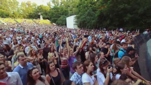 MOSCOW, RUSSIA - AUGUST 23, 2011: View of cheering people at summer live concert. Music band performing on stage. Crowd. Raise hands