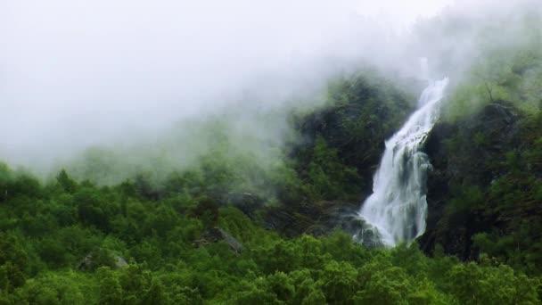 Pohled na vodopád cascade v zeleném lese mezi horami. Letní den. Hluboké mlha. Příroda. Nikdo