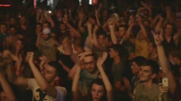 Petrohrad, Rusko - 26 června 2015: Lidé rytmicky tleskat na koncertu v nočním klubu v etapě. Bodová světla. Fandění. Člověk má sekeru