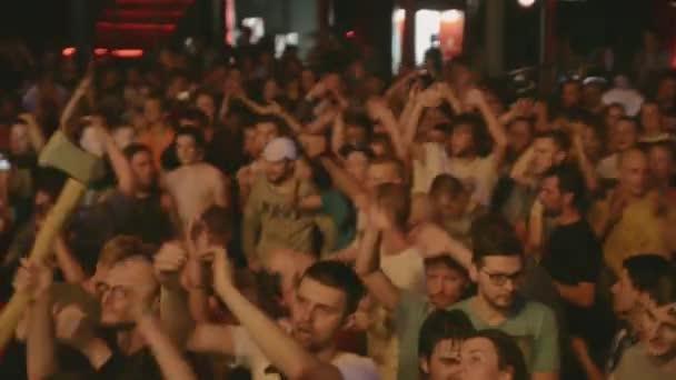 Petrohrad, Rusko - 26 června 2015: Lidé rytmicky tleskat na koncertu v nočním klubu v etapě. Bodová světla. Zvedněte ruce. Člověk má sekeru