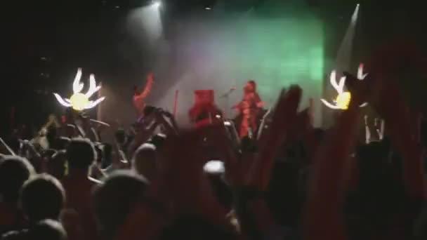 Petrohrad, Rusko - 26 června 2015: Lidé tleskat na koncertu v nočním klubu v etapě. Bodová světla. Fandění. Medvěd, dvě zpěvák na scéně