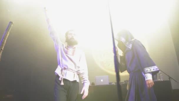Petrohrad, Rusko - 26 června 2015: Bearded zpěvák v plášti, chlape v lidových tričko luk, rozloučit na jevišti v nočním klubu. Světelné kužele