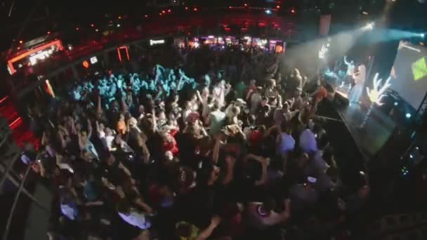 SAINT PETERSBURG, RUSSIA - JUNE 26, 2015: People cheering at live performance in nightclub. Spotlights. Folk rock band performing on stage