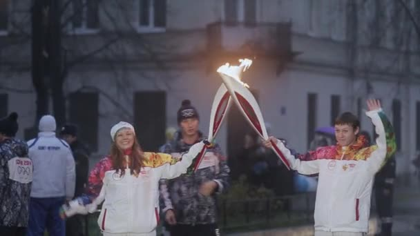 Petrohrad, Rusko - 27 října 2013: štafeta olympijského ohně v Petrohradu. Světlonoš světle pochodní šťastná žena. Vlna ruka