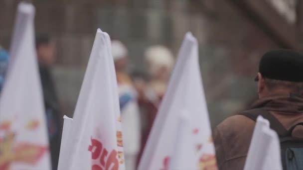 Petrohrad, Rusko - 27 října 2013: štafeta olympijského ohně v Petrohradu. Mužské světlonoš v uniformě říkat projev na jevišti. Příznaky