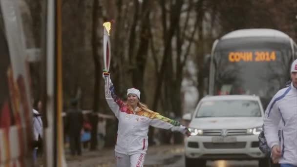 Petrohrad, Rusko - 27 října 2013: štafeta olympijského ohně v Peterhof, Petrohrad. Šťastné ženy světlonoš s plamenem