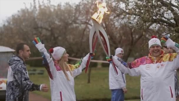 Petrohrad, Rusko-27. října 2013: závod na přenos olympijských plamenů v Petrohradě Peterhof. Torchnositel podlehl ohni v parku ženě