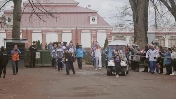 SAINT PETERSBURG, RUSSIA - OCTOBER 27, 2013: Relay race Olympic flame in Peterhof, Saint Petersburg. Cortege with female torchbearer run in park