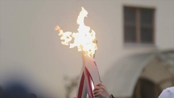 SAINT PETERSBURG, RUSSIA - OCTOBER 27, 2013: Relay race Olympic flame in Saint Petersburg in October. Process of pass flame between torchbearers