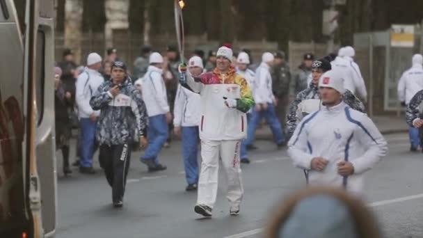 Petrohrad, Rusko-27. října 2013: závody v Petrohradě olympijský plamen. Mužský muž se s ohněm roznese. Stráže. Publikum