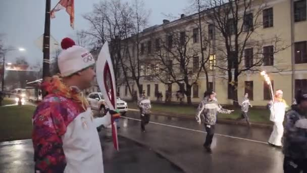 SAINT PETERSBURG, RUSSIA - OCTOBER 27, 2013: Relay race Olympic flame in Saint Petersburg. Torchbearer run with flame to another man. Evening