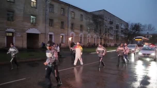 Petrohrad, Rusko-27. října 2013: závody v Petrohradě olympijský plamen. Ten s ohněm běží. Večer. Déšť. Kortege