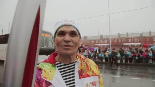 Petrohrad, Rusko-27. října 2013: Bari, který se v Petrohradě účastní přenosu olympijského ohně. Déšť. Gesto