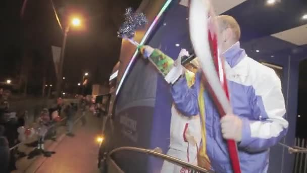 SAINT PETERSBURG, RUSSIA - OCTOBER 27, 2013: Relay race of Olympic flame in Saint Petersburg. Supporters wave pom pom from bus. Singer. Dance