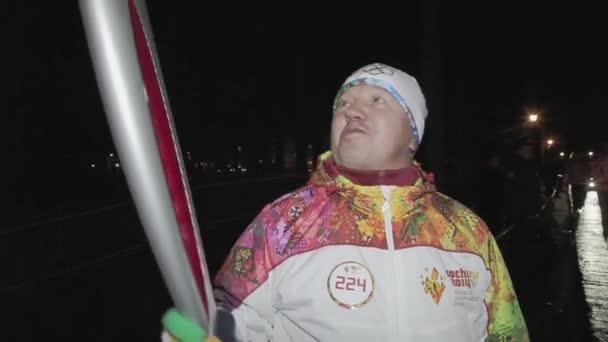 Petrohrad, Rusko-27. října 2013: dospělý člověk, člen závodu olympijského ohně v Petrohradu, dává interview. Temný večer