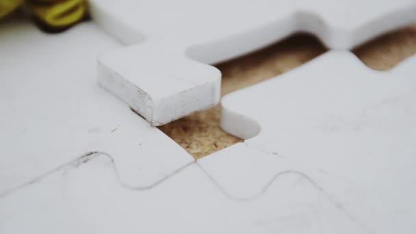 Muž se rozvrhnout chybějící část bílé velké mozaiky. Podrobnosti. Stavba