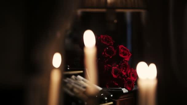 Weiße Kerzen brennen. Feuer. Strauß roter Rosen auf Hintergrund. Flamme