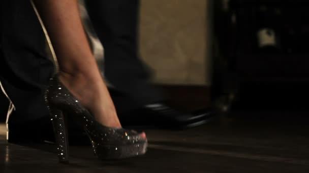 Beine gehen Mann und Frau in glühenden Schuhen auf Stöckelschuhen über den Boden. offizieller Stil