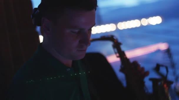 DJ točí na gramofonu. Muž hrát saxofon. Párty v nočním klubu. Hudebníci
