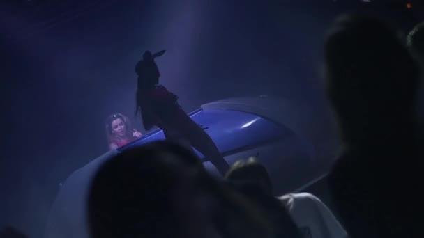 Silhouette mc Mädchen in Hasenmaske Tanz in einem Nachtclub. DJ-Mädchen am Plattenteller. Menschen