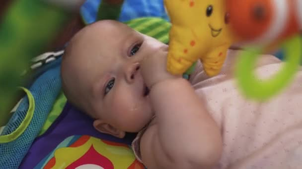 Malé dítě leží v postýlce hraje s hračkami. Dítě. Fajn. Rodina. Mateřství.