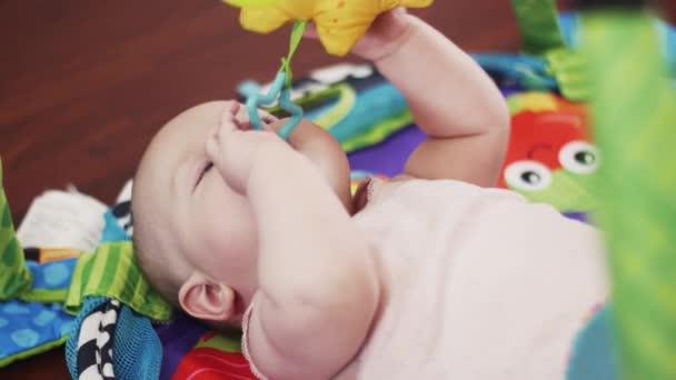 Rozkošné miminko leží na koberci děti hrát si s hračkami. Fajn. Mateřství
