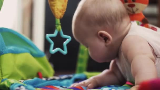 Adorable little baby playing with toys on colorful developing children rug.