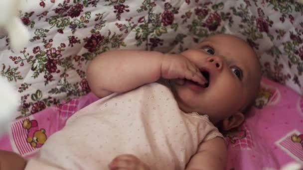 Imádnivaló baba aranyos kiságy rejlik. A kezedet a szájban. Gyermek. Anyaság.
