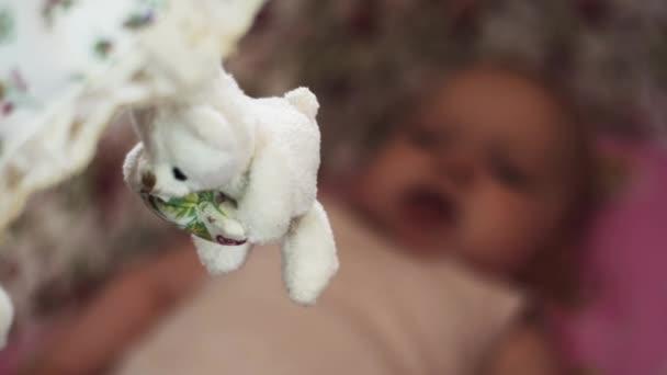 Roztomilá malá dítě leží v postýlce. Předsazení bílé hračka medvěda. Dítě. Mateřství