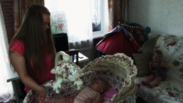 Mladá matka swing roztomilý betlém s malým dítětem. Mateřství. Štěstí