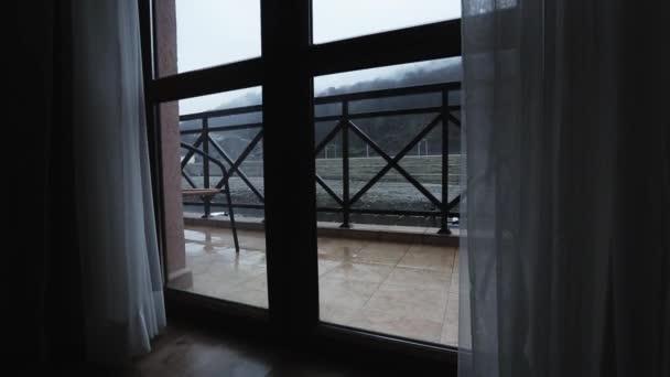 Zobrazit okno kapky deště padají na verandě. Šedá obloha. Hory z okna