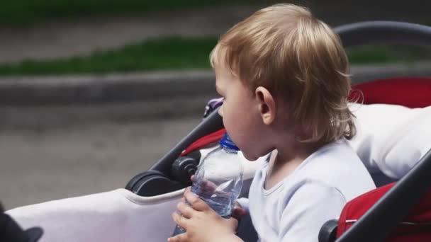 Kleinen blonden Jungen Trinkwasser aus Flasche im Kinderwagen. Sommertag. Kind