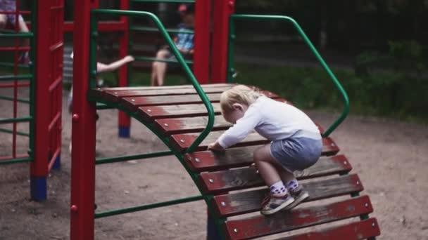 Little boy playing on children slide on playground in summer park. Walking