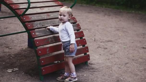 Malý kluk hraje na snímku děti na hřišti v letním parku. Dětství