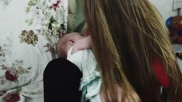 Mutter im roten Hemd, die ihr kleines Baby auf dem Sofa stillt. Mutterschaft. Gesundheit.