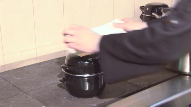 Cook v jednotné koktejl stojící pokryta pánev na sporák v kuchyni restaurace pracovní. Vaření. Ručník
