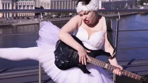 Lány a balerina fehér ruha játék elektromos gitár napsütéses napon a tengerparton. Crazy dance. Rock