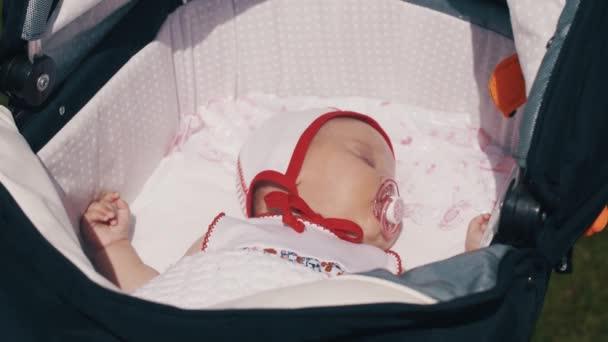 Little baby sleep in baby carriage. Baby dummy.Summer sunny day. Motherhood