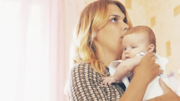 Young mother holding little cute baby with blue eyes. Motherhood. Family. Kiss