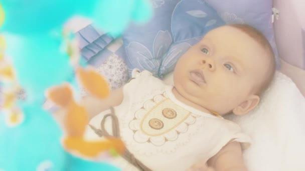 Aranyos baba kiságy rejlik. A mozgó játékok, gyermek felett. Anyaság. Anyai