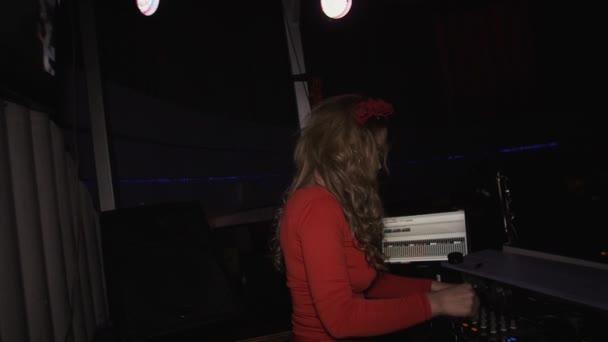 DJ lány piros ruhában, fonó, lemezjátszó, buli, szórakozóhely. Tánc. Keverés