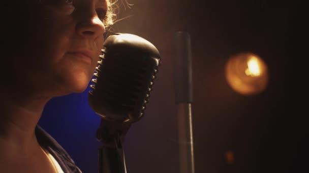 Scrubwoman scream in vintage microphone on stage of club. Smoke. Spotlight